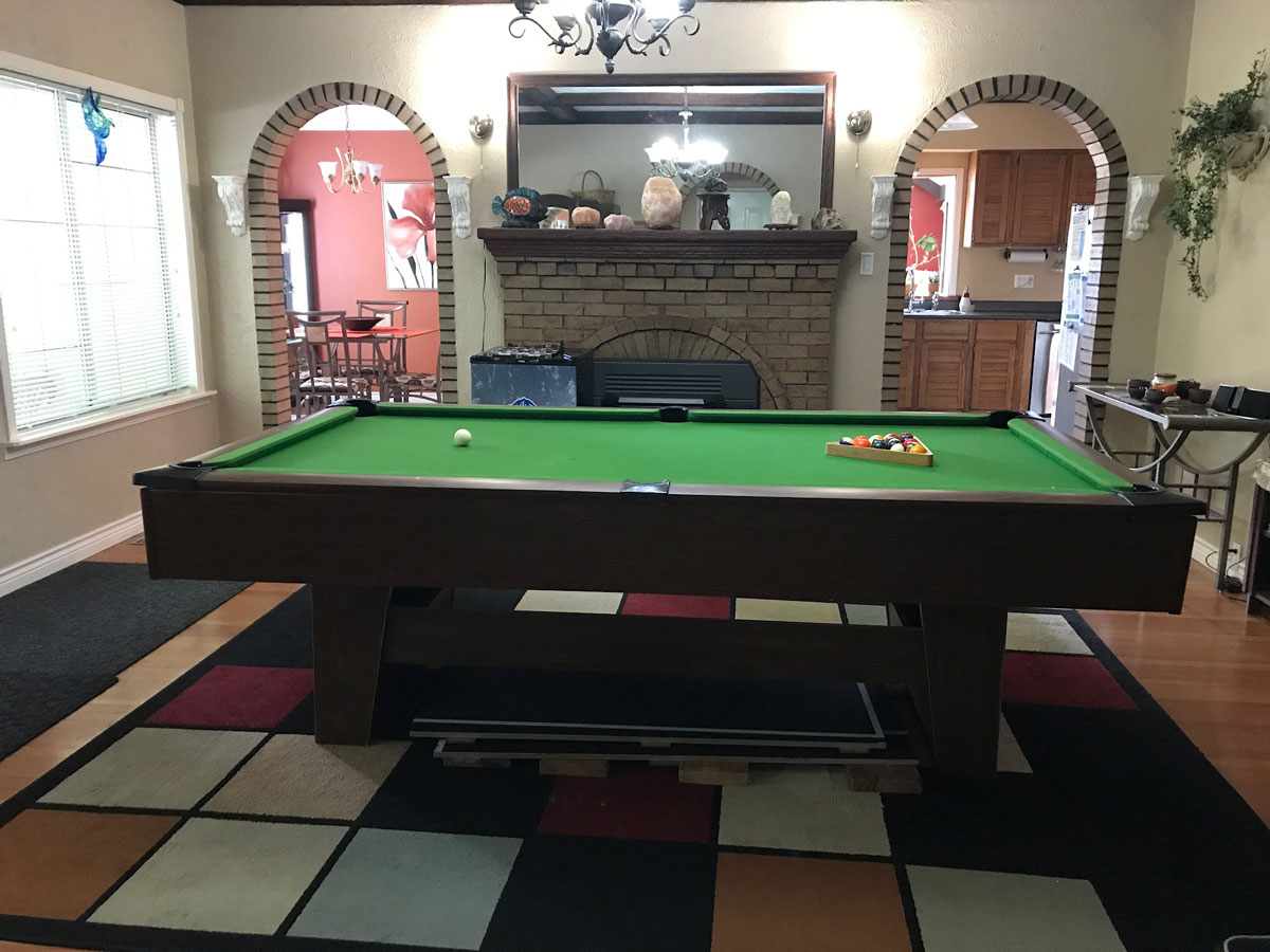 Games room with pool table, fireplace and mirror and large checkered rug. Perfect for traveling guests and their families.