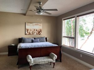 Massive windows with large bed and view of lake from master bedroom in this Lakeview Rental Home
