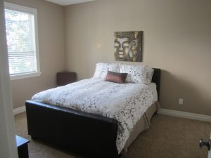 Spasre bedroom with neutral walls and bright bedding and art on wall