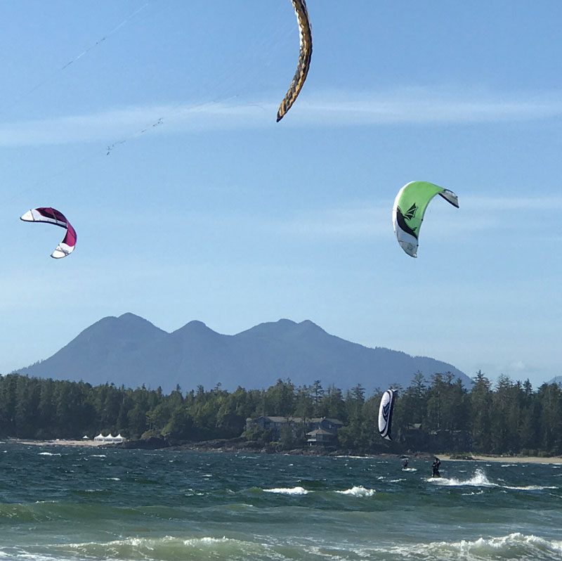 Wind surfers with blue skies, trees and mountains in background