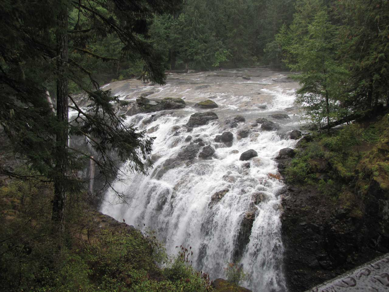 Massive rocky waterfall surrounded by forest British Columbia
