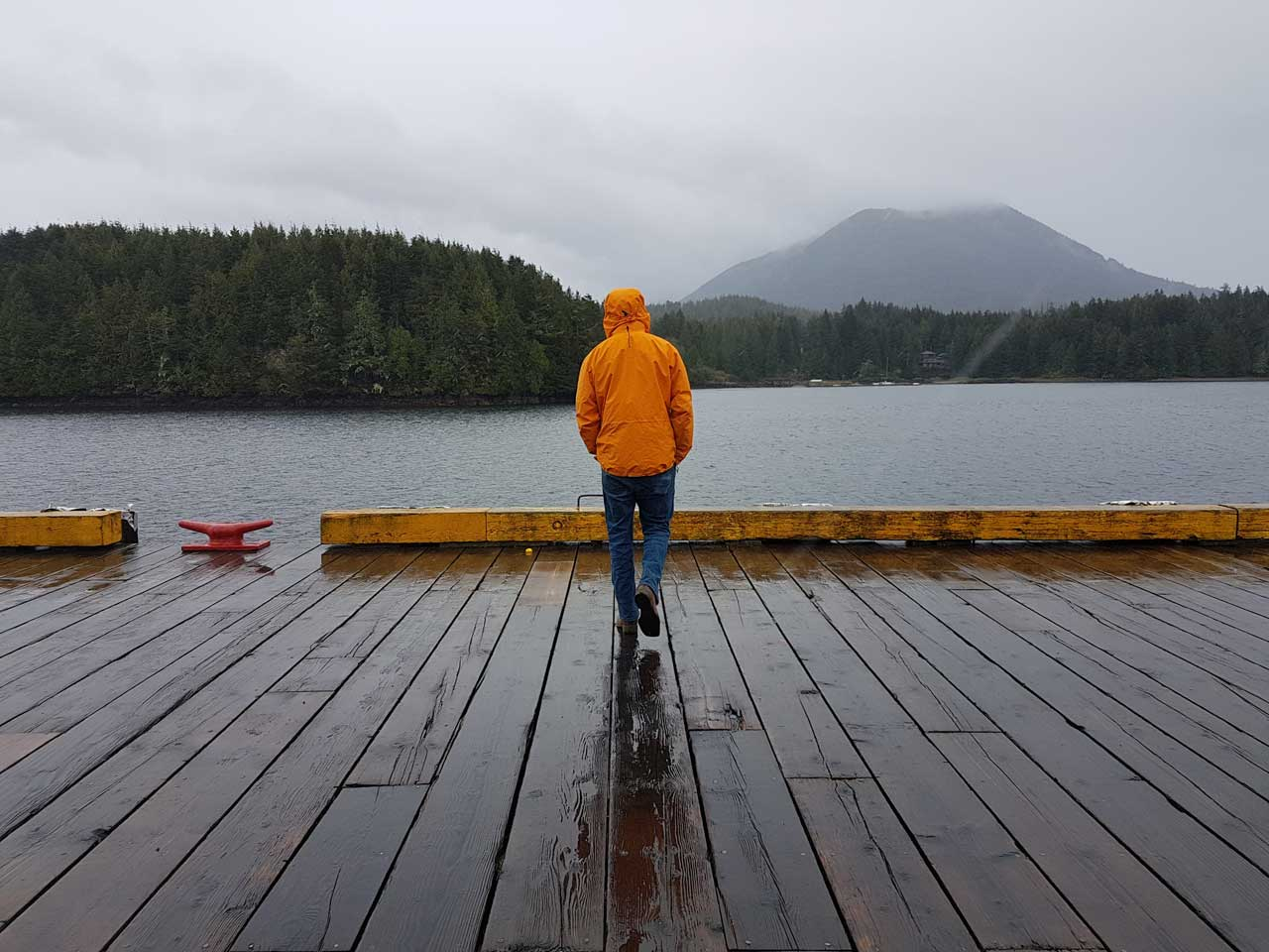 Man in orange rain coat standing on dock with ocean in background on rainy day