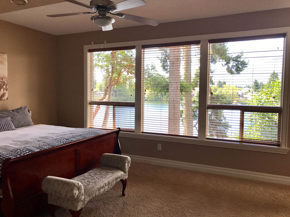 Massive windows with spectacular view of lake from master bedroom in this Lakeview Rental Home
