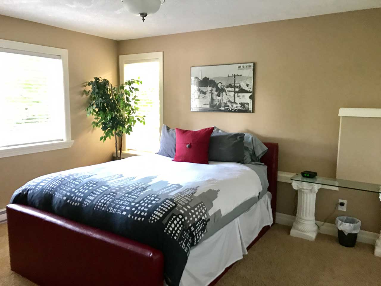 Lakeside suite bedroom with art on wall and fresh clean linens on bed