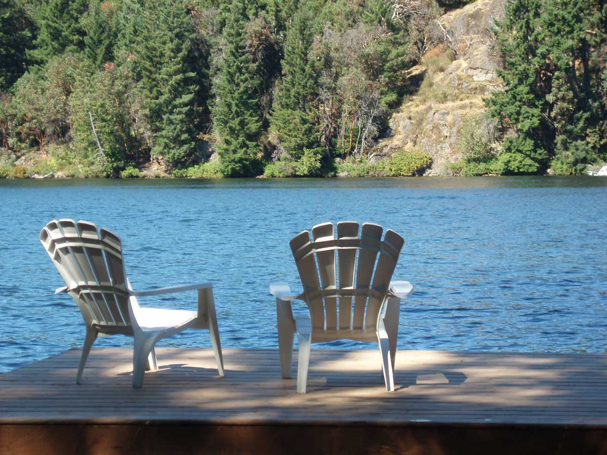 2 white chairs on a dock overlooking Long Lake at an executive rental home