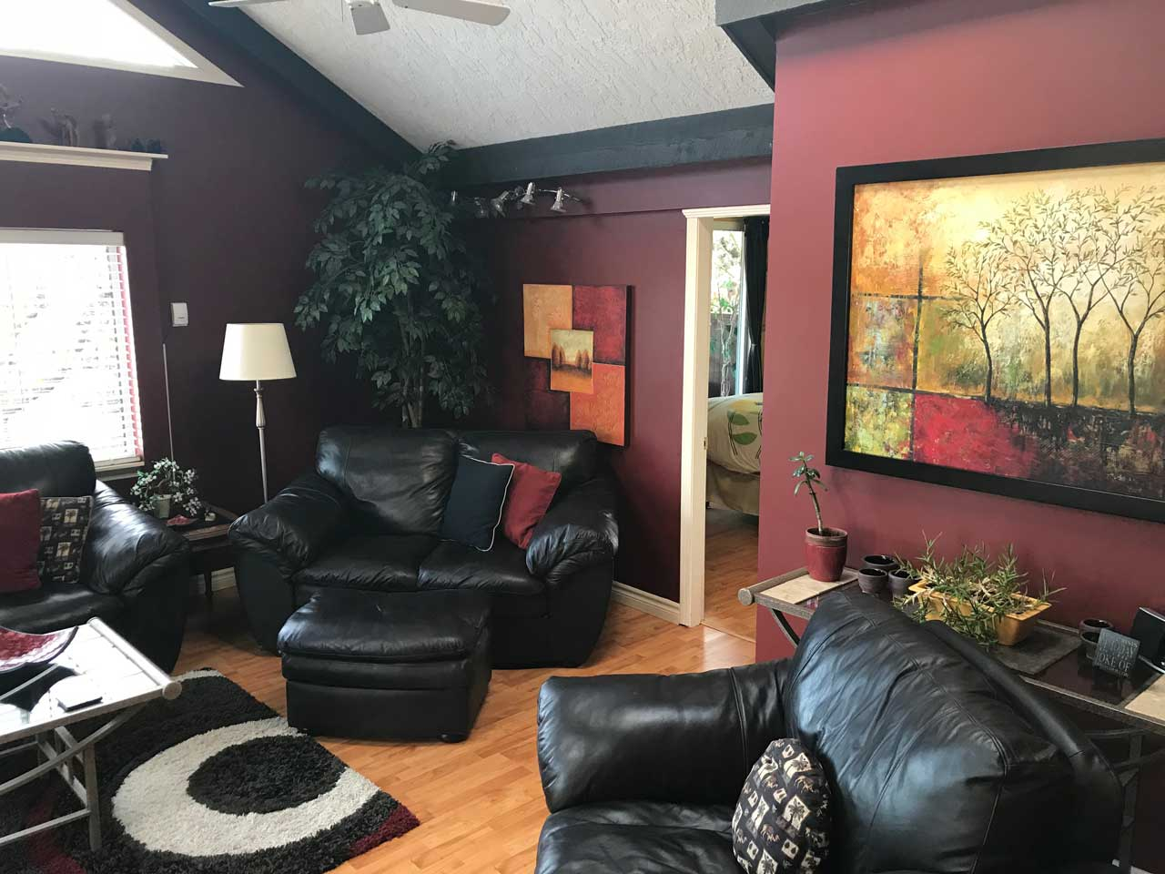 Garden Paradise living room leather couches and colorful art
