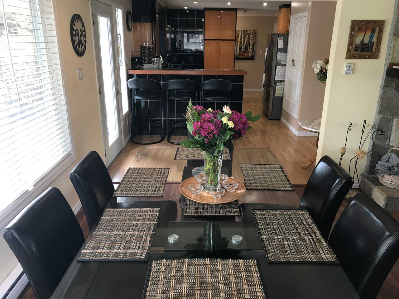 Lakeview home dining area with fresh flowers and kitchen in background